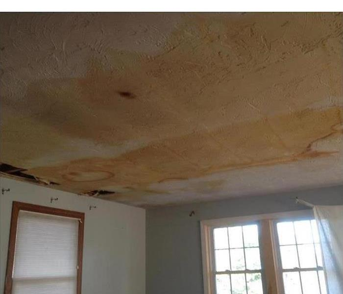 Water damaged ceiling showing dark staining to drywall