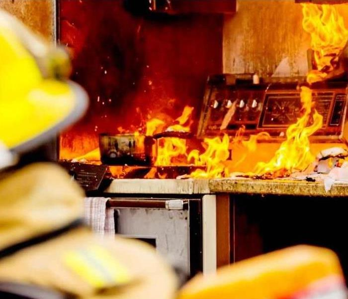 shows a kitchen on fire with a firefighter looking on.