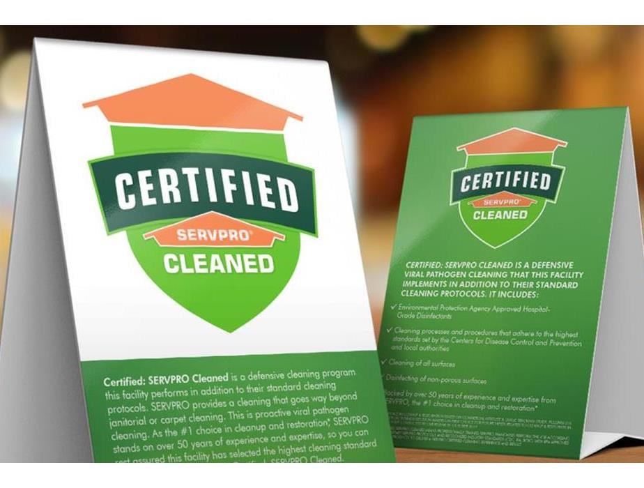Two white and green table signs with Certified: SERVPRO Cleaned logo including description of services and key points.