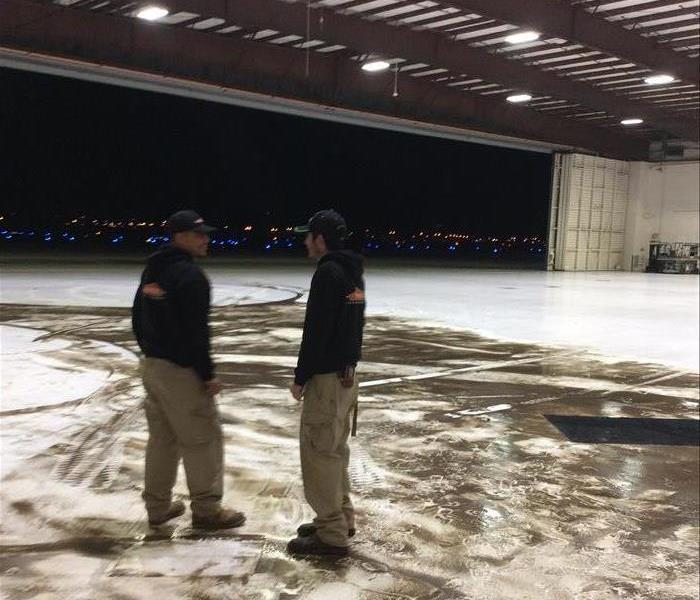 two employees standing in an airplane hangar. Water and dirt smeered on the ground in the background