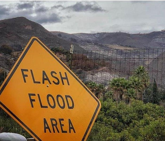 Background shows burned terrain, mountains. Flash Flood Yellow Sign